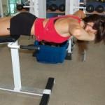 Гиперэкстензии на горизонтальной скамье без прогиба в верхней точке, руки за головой. Упражнение для упругих ягодиц и мышц задней поверхности бедра.